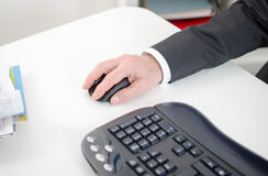 Businessman holding a computer mouse Stock Photos