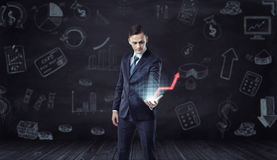 Businessman holding computer projection of rising red arrow on the background with economic sketches. Profit growth indicator. Modern technology. Success and Stock Image