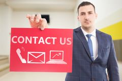 Businessman holding contact us paper with symbols stock images