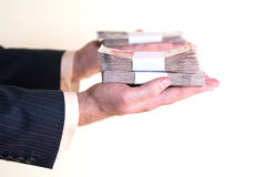 Businessman holding couple of money stacks Royalty Free Stock Images