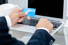 Businessman holding credit card by a laptop keyboard Royalty Free Stock Photos