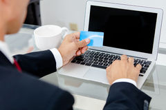 Businessman holding credit card by a laptop keyboard Royalty Free Stock Photography