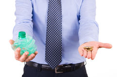 Businessman holding crushed bottle and coins. Royalty Free Stock Photography