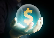 Businessman holding crystal ball with dollar sign Stock Photo