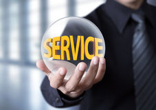 Businessman holding crystal ball with service concept Stock Photo