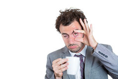 A businessman holding a cup of beverage and trying hard to stay awake royalty free stock image