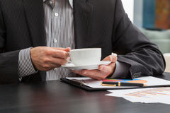 Businessman holding a cup of coffee Royalty Free Stock Photos
