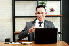 Businessman holding a cup of coffee behind laptop Royalty Free Stock Images