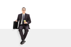 Businessman holding a cup of coffee seated on panel Royalty Free Stock Image