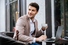 Businessman holding cup of coffee and working with laptop outdoors Stock Photos