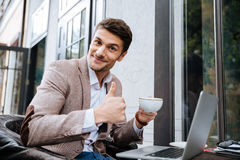 Businessman holding cup of coffee and working with laptop outdoors. Smiling young handsome businessman holding cup of coffee and showing okay sign in cafe Royalty Free Stock Photos