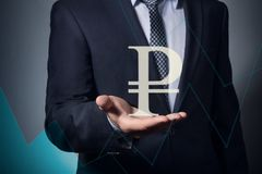 Hand holds the ruble symbol. Businessman holding currency symbol in hands. hand holds the ruble symbol royalty free stock photography