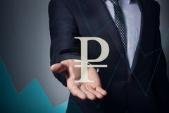 Hand holds the ruble symbol. Businessman holding currency symbol in hands. hand holds the ruble symbol royalty free stock photo