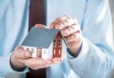 Businessman Holding a Cute Miniature House Model Stock Photo