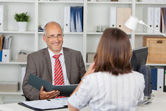 Businessman Holding Cv Of Female Candidate At Desk Royalty Free Stock Images