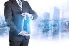 Businessman holding 3d building model Stock Images