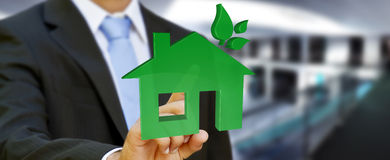 Businessman holding 3D eco house and energy efficiency Royalty Free Stock Photos