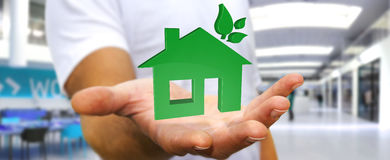 Businessman holding 3D eco house and energy efficiency Royalty Free Stock Image