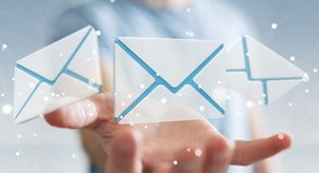 Businessman holding 3D rendering flying email icon in his hand. Businessman on blurred background holding 3D rendering flying email icon in his hand Stock Photography
