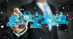 Businessman holding 3D rendering group of blue people. Businessman on blurred background holding 3D rendering group of blue people Stock Photos