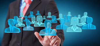 Businessman holding 3D rendering group of blue people Stock Photo