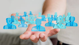 Businessman holding 3D rendering group of blue people Royalty Free Stock Photo
