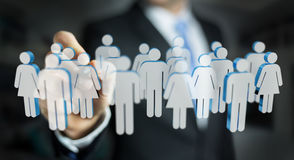 Businessman holding 3D rendering group of people in his hand Stock Photos