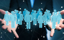Businessman holding 3D rendering group of people in his hand Stock Photography