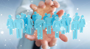 Businessman holding 3D rendering group of people in his hand. Businessman on blurred background holding 3D rendering group of people in his hand Royalty Free Stock Photo