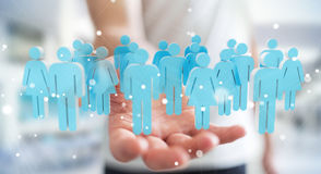 Businessman holding 3D rendering group of people in his hand. Businessman on blurred background holding 3D rendering group of people in his hand Royalty Free Stock Images