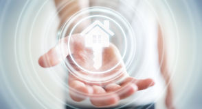 Businessman holding 3D rendering icon house in his hand. Businessman on blurred background holding 3D rendering icon house in his hand Stock Photo