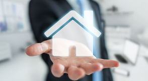 Businessman holding 3D rendering icon house in his hand. Businessman on blurred background holding 3D rendering icon house in his hand Stock Photography