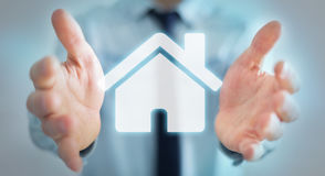 Businessman holding 3D rendering icon house in his hand. Businessman on blurred background holding 3D rendering icon house in his hand Stock Images