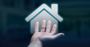 Businessman holding 3D rendering icon house in his hand. Businessman on blurred background holding 3D rendering icon house in his hand Royalty Free Stock Photography