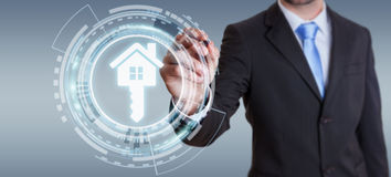 Businessman holding 3D rendering icon house in his hand. Businessman on blurred background holding 3D rendering icon house in his hand Royalty Free Stock Images