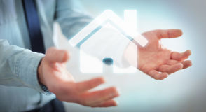 Businessman holding 3D rendering icon house in his hand. Businessman on blurred background holding 3D rendering icon house in his hand Stock Image
