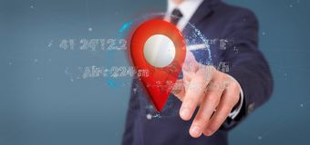 Businessman holding a 3d rendering pin holder on a globe with co. View of a Businessman holding a 3d rendering pin holder on a globe with coordinates Stock Photos