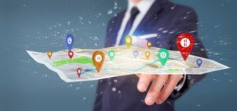 Businessman holding a 3d rendering pin holder on a map. View of a Businessman holding a 3d rendering pin holder on a map Royalty Free Stock Photo