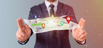 Businessman holding a 3d rendering pin holder on a map. View of a Businessman holding a 3d rendering pin holder on a map Stock Images