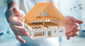 Businessman holding 3D rendering unfinished plan house in his ha. Businessman on blurred background holding 3D rendering unfinished plan house in his hand Royalty Free Stock Images