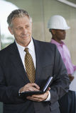 Businessman Holding Dairy With Male Architect Stock Photos