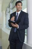 Businessman Holding Dairy By Window Royalty Free Stock Image
