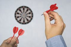 Businessman holding a dart aiming at the target - business targeting, aiming, focus concept. hit the target. Success in business. Businessman holding a dart royalty free stock image