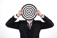 Businessman holding a dartboard. Businessman with a dart in bull's eye Stock Photography