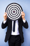 Businessman holding dartboard Stock Images