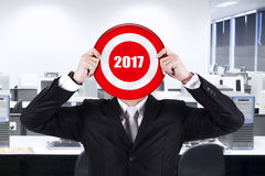 Businessman holding a dartboard with number 2017 Royalty Free Stock Photo
