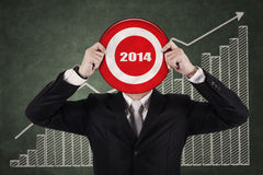 Businessman holding a dartboard. Businessman holding a target board with year 2014 writing in the middle Stock Image