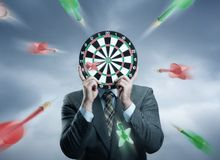 Businessman holding darts board in his hands Stock Photography