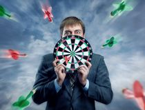 Businessman holding darts board in his hands Stock Images
