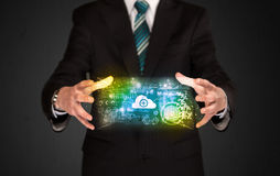 Businessman holding data cloud. Businessman holding a shining data cloud in front of his body Royalty Free Stock Photos